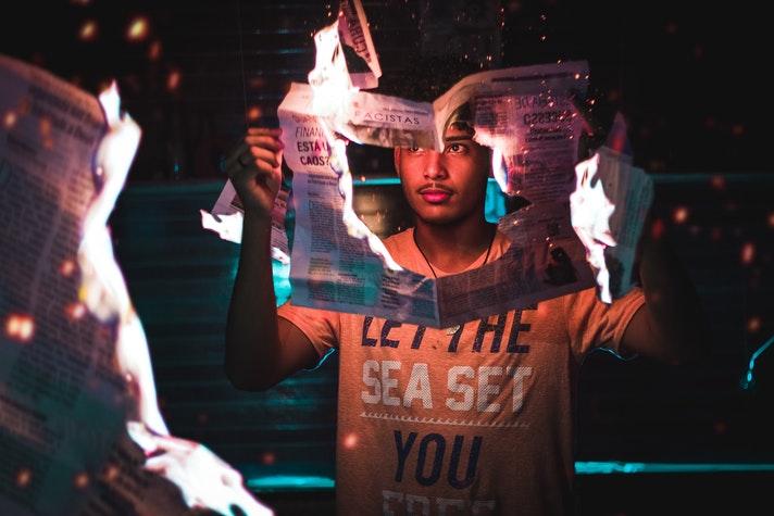 Hombre joven sosteniendo un periódico en llamas.